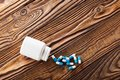 Medical blue pills and white bottle on wooden background. Royalty Free Stock Photo