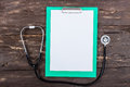 Medical clipboard and stethoscope on dark wooden table. Royalty Free Stock Photo