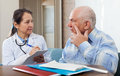 Medical consultation senior patient and doctor talking at table Stock Images
