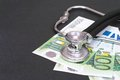 Medical costs stethoscope draped on euro hundreds for your healthcare copy focus is on the bottom of the stethoscope copy space to Royalty Free Stock Photos