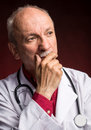 Medical doctor with stethoscope on a dark red background Royalty Free Stock Photo