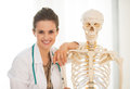 Medical doctor woman near human skeleton portrait of smiling anatomical model Royalty Free Stock Photography