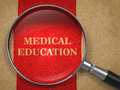 Medical education magnifying glass concept on old paper with red vertical line background Stock Photo