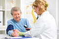 Medical exam doctor measuring blood pressure of senior patient Royalty Free Stock Photo
