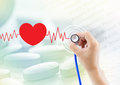 Medical, hand holding stethoscope, heart beat graph and pill Royalty Free Stock Photo