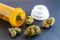 Medical marijuana buds on black background in spilling out of prescription bottle with branded cap Royalty Free Stock Image