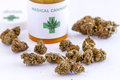 Medical marijuana buds and seeds sitting on white table top next to cannabis prescription bottle with lid Royalty Free Stock Photo
