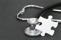 Medical mystery puzzle piece leaning on a stethoscope focus is on the puzzle piece for your mysteries questions help and problems Stock Photography