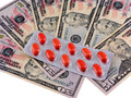 Medical pills on dollars bank note as symbol for high costs set Stock Photo