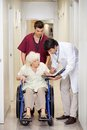 Medical professionals with patient in corridor doctor communicating disabled senior female hospital Stock Photo