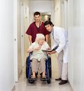 Medical professionals with patient in corridor portrait of doctor and male technician disabled senior female hospital Stock Photos