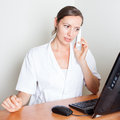 Medical receptionist calling sets appointment with visitor on phone Royalty Free Stock Photo