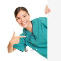 Medical sign person woman showing blank poster billboard placard pointing young female nurse or medical doctor professional in Stock Photography