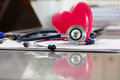 Medical stethoscope head and red toy heart lying on cardiogram c