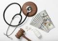 Medical stethoscope, pills, judge hammer and money on white back Royalty Free Stock Photo