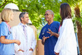 Medical team having discussion outdoors looking at each other wearing scrubs Royalty Free Stock Images