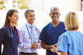 Medical team having discussion outdoors wearing scrubs smiling Stock Photography
