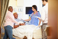 Medical team meeting with senior couple in hospital room examining patient Stock Photo