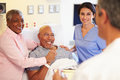 Medical team meeting with senior couple in hospital room looking at each other smiling Stock Photos