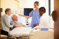 Medical team meeting with senior couple in hospital room worried having a discussion Royalty Free Stock Photos