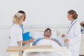 Medical team taking care of a sick patient lying in his sickbed Royalty Free Stock Image
