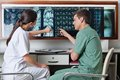 Medical technicians pointing at mri x ray two of patient Stock Image