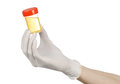 Medical theme: doctor's hand in white gloves holding a transparent container with the analysis of urine on a white background Royalty Free Stock Photo