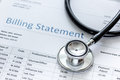 Medical treatmant billing statement with stethoscope on stone background Royalty Free Stock Photo