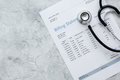 Medical treatmant billing statement with stethoscope on stone background top view mockup Royalty Free Stock Photo