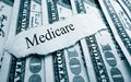Medicare bills paper headline on hundred dollar Royalty Free Stock Images