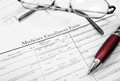 Medicare enrollment form document with glasses and pen Stock Images