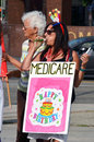 Medicare rally los angeles ca july a demonstrator holding a sign which features a birthday cake and the word blows a noisemaker Stock Images