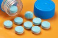 Medicinal tablets with blue container and cap on an orange table Royalty Free Stock Images