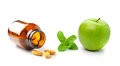 Medicine bottle of brown glass pill apple and mint   on Royalty Free Stock Photo