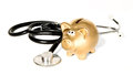 Medicine stethoscope with golden money-box Royalty Free Stock Photo