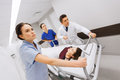 Medics with woman on hospital gurney at emergency profession people health care reanimation and medicine concept group of or Stock Images