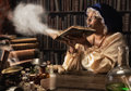 Medieval alchemist blowing dust off the old books in her laboratory Royalty Free Stock Photography