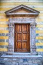 Medieval ancient wooden door with ornate stone columns, Italy. Royalty Free Stock Photo