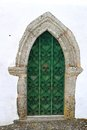 Medieval door green wooden with ornate ironwork that goes to a point at the top on a white washed wall Stock Photography
