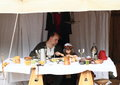 Medieval family little girl and her father dressed in gothic clothes sitting by the table and eating in camp Stock Photo
