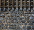 Medieval gate bars on castle stone wall Royalty Free Stock Photo