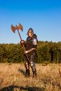 Medieval knight in the field with an axe Royalty Free Stock Photos