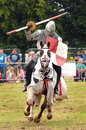 A medieval knight holding his lance ona horse galloping with chainmail and english colors Stock Photos