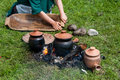 Medieval lifestyle scene pots and dishes being cooked on fire and girl washing the wooden bowl Royalty Free Stock Images