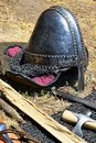 Medieval norman type conical helmet with nose protection piece and sides protected with chainmail placed on fabric filler next to Royalty Free Stock Photo