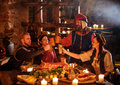 Medieval people eat and drink in ancient castle kitchen interior Royalty Free Stock Photo