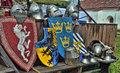 Medieval shields and helmets a row of silver metal laying with banners chain male Royalty Free Stock Photography