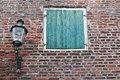 Medieval wall with lamp and green blind Royalty Free Stock Photo