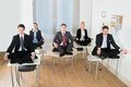Meditating businesspeople sitting on desk with their legs crossed in office Stock Images