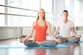 Meditating in gym portrait of healthy girl and guy doing exercise for relaxation Royalty Free Stock Photos